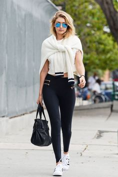 Gigi Hadid does sporty chic in zippered leggings, a tied sweater knit, classic Adidas, and aviators