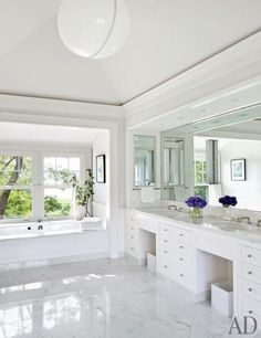 In a Hamptons home updated by Shelton, Mindel & Associates, a marble-floored bath includes an acrylic pendant light from ABC Carpet & Home.  Pin it.