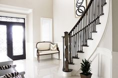 Front entrance, curved staircase, foyer settee, black white DIY art, painted staircase, black white brass Regency style