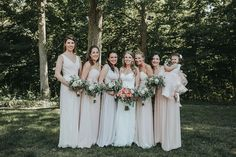 Outdoor wedding party: bridesmaids in light blush mismatched dresses and white peony wedding bouquets.