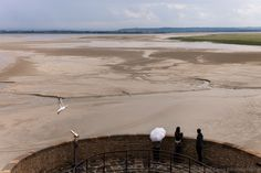 https://flic.kr/p/of9JHM   Observers, Mont Saint-Michel   Landscape view of the low tide and Normandy coast by cloudy weather from the battlements of the Mont Saint-Michel, a UNESCO world heritage site situated in Normandy, France.  Website   Google+     Blog   Tumblr   Twitter   Pinterest   Getty Images  Follow me on Facebook