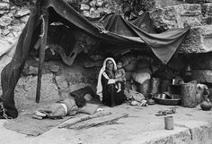 Arab Refugees Living in Ruins  A Palestinian mother and her two children camped out in the ruins of a Roman amphitheater in Jordan. After the partitioning of Israel, many Arab families found themselves refugees in what was formerly their homeland and found that they had to move. Stock   Date Photographed: 1949