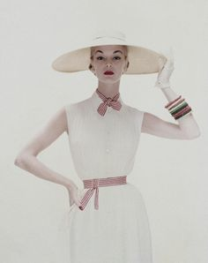 May 1954. Wearing a white tucked crepe dress, of Dacron and rayon, tied with red and white stripes, by David Crystal; the hat, a wide circle of straw banded with white chiffon.