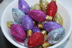 Unscrew the bulbs, and coat each one with some Elmers glue. Sprinkle glitter all over & tap to remove excess.  Set to dry & figure out how you will display these sparkling beauties!  On a wreath?  In a bowl?  Gift tags?  Ornaments?