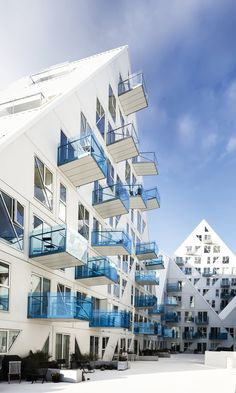 "Isbjerget (Iceberg): apartments at Aarhus Port, Aarhus, Denmark - photo by Ida Schmidt, via bobedre.dk; designed by the Danish architectural firms CEBRA and JDS Architects, SeARCH, and Louis Paillard; ""The balconies feature glass panels of deep blue on the lower levels up to transparent at the top adding to the iceberg-look of the housing structure."" - comment from designboom"