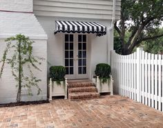 simple but full of little things that make this a great space - brick pavers, striped scalloped awning, box planters, decorative yet functional fence....
