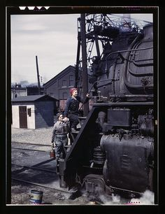 "Women wipers of the Chicago and North Western Railroad cleaning one of the giant ""H"" class locomotives, Clinton, Iowa. Mrs. Marcella Hart and Mrs. Viola Sievers. Delano, Jack,, photographer."