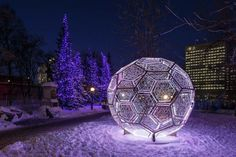 A giant ball of light statue that lights up the dark at the Winterlude Pavilion in Ottawa, Canada.