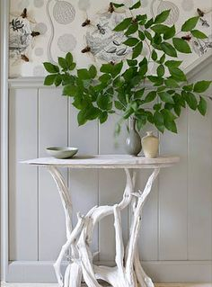 table with a branch base topped with leaves. note the wallpaper, bringing the outside in