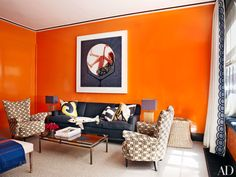 A custom-mixed persimmon paint splashes the library, where an Ormond Gigli photograph surveys a vintage T. H. Robsjohn-Gibbings sofa in a Loro Piana Interiors fabric. The lamps are by Simon Pearce, the 1950s Italian lounge chairs are clad in a velvet by Eric Cohler Design for Lee Jofa, and the cocktail table is from Flair.
