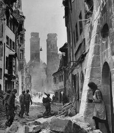 A local watches American soldiers inspect a street for snipers. Nuremberg, 1945.   David E. Scherman