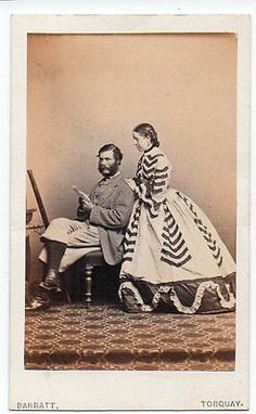 1860's Woman in a wildly trimmed day dress posing with her husband.