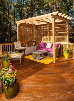 Jolie pergola en bois abritant un petit coin détente sur une spacieuse terrasse en pleine nature