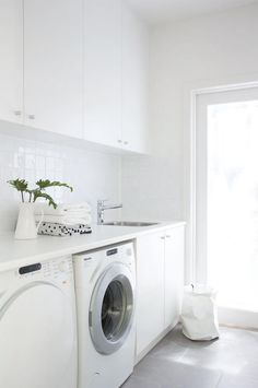 Modern white laundry room features white cabinets paired with white countertops and a white grid tiled backsplash. Modern white laundry room features white cabinets paired with white countertops and a white grid tiled backsplash. Laundry Nook, Laundry Room Layouts, Laundry Room Cabinets, Laundry Room Organization, Laundry Storage, Small Laundry, Laundry In Bathroom, Garage Laundry, Kitchen Cabinet Layout