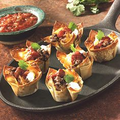 Mini Tacos!  Fill wonton shells with cooked taco beef, salsa + cheese.  Honestly takes 5 minutes to bake at 425.  Could not be easier or tastier!  You could actually put anything you want in these, eggs + bacon + cheese, maybe dessert fillings, the possibilities are endless! Love love them!