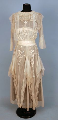 Circa 1900-1920s tea gown: cream net with square collar and flared elbow length sleeve having an over skirt with four long ruffled points, embroidered with a stylized floral.