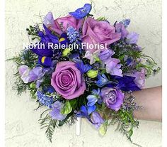 Round bouquet made with lavender Roses, grape Hyacinth, Sweet Pea, purple Lisianthus, blue Delphinium, caspia and blue Iris.