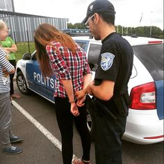 Student tests the feeling of being handcuffed at police information day.
