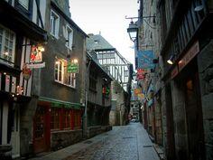 Dinan: Pittoresca strada lastricata fiancheggiata da vecchie case, con ristoranti e piccoli negozi - France-Voyage.com