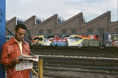 """""""Lee"""" whole car at 180th Street, with a man reading a newspaper on the platform. Bronx, 1980 
