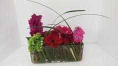 Beautiful intricate low centerpiece, pink stock, red gerbera daisy, green hydrangea,