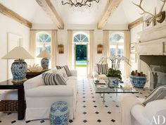 Ralph Lauren Home fabrics cover the sofa and pillows in the poolhouse, which features 16th-century Belgian pine ceiling beams and a 17th-century French limestone mantel; the lamps are made from 18th-century Chinese vessels.