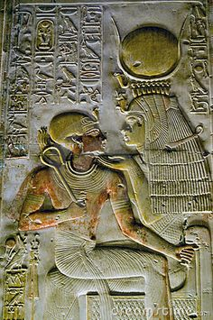 An ancient Egyptian hieroglyphic carving showing the goddess Isis - wearing the crown of Hathor - with the young Pharoah Seti on her lap. Wall of the temple of Abydos in Egypt
