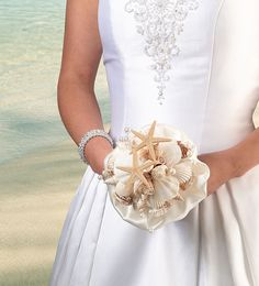 "For beach-themed and destination weddings, this seashell bouquet makes a great accessory for the bride to hold. The clear acrylic handle holds a bouquet made of an ivory satin ruffle and a collection of different seashells and starfish. Size: Width = 6"". Length = 6.5""."
