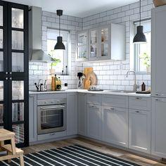 Ett litet kök i grå och vit traditionell stil med grå och svartbetsade LERHYTTAN glasdörrar.