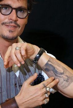 Johnny Depp showing a tattoo of a photograph of his mother when she was younger.  She's in her waitress uniform when she worked in a diner.