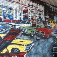 This wall mural is a tribute to the age of muscle cars and features a classic Challenger among some fast company