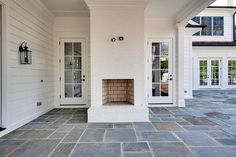 Fantastic covered patio features a white brick outdoor fireplace alongside slate tiled floors.