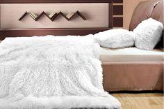 Chlpaté prikrývky a deky bielej farby na posteľ