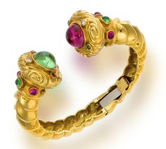 An eighteen karat gold, tourmaline and diamond bracelet designed as a hinged cuff with scrolling terminals set with pink and green cabochon tourmalines, accentuated by circular-cut and cabochon tourmalines, and round brilliant-cut diamonds; gross weight approximately: 87.9 grams; diameter: 2 1/4in.