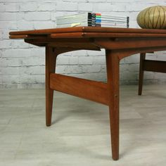 A truly fantastic piece of Danish engineering! Manufactured by Trioh of Denmark this Teak coffee table is designed to cleverly convert into a dining table big enough to seat six people! Converts quickly and easily by lifting to achieve the correct height then simply pulling out each extension leaf, hey presto the dinner party is on! Stunning patina and restored condition, an iconic piece of craftsmanship. Dimensions: As a Coffee Table:L: 135cm W: 50cm H: 52cm As a Dining Table:L: 135cm W…