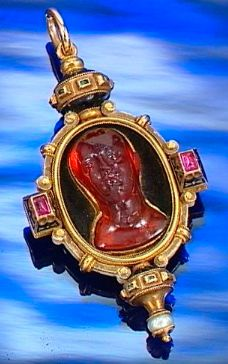 ENAMELLED GOLD, GEM-SET AND AMBER PENDANT, CASTELLANI, CIRCA 1865. Centring on a carved amber cameo carved to depict the frontal profile of a Classical  Emperor,  within a black and white enamel oval-shaped frame of  Renaissance revival design, accented to the cardinal points with cabochon rubies, emeralds and a pearl, applied to the reverse with makers monogram.