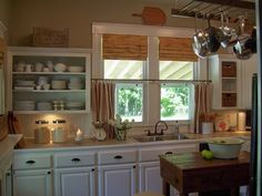 old ladder hung from the ceiling as a pot rack?  Also like the open shelves and handmade barnwood island.