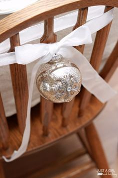 Tie a pretty ornament to the back of a chair in the dining room for Christmas decor -- simple and beautiful! | JustAGirlAndHerBlog.com