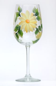 Sunny yellow daisy petals with soft white highlights, yellow centers and deep green leaves hand-painted on quality 18.5 ounce wine glass.