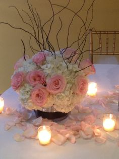 Wedding centerpiece of white hydrangea and pink roses in diamond banded cylinder with curly willow surrounded by rose petals and votive candles