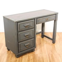 This shabby chic desk is featured in a solid wood with a distressed gray chalk paint finish. This desk has 4 spacious drawers, unique carved handles with brass pulls and a black leather writing top. Eclectic desk great for storing a laptop and paperwork! #shabbychic #desks #writingdesk #sandiegovintage #vintagefurniture