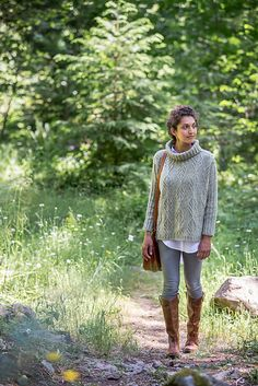 Delicate cables form decorative oak leaf medallions to paper the extra-wide fabric of this poncho-like pullover. On a ground of reverse stockinette, the cable motifs stand in relief like woodblock carvings. Side vents and exaggerated drop shoulders give this garment easy style, while a loose turtleneck provides a double layer of warmth around your neck. Birch Bay's front and back are knit flat and sewn together; stitches for the double-ribbed sleeves and neck are picked up and worked in the…