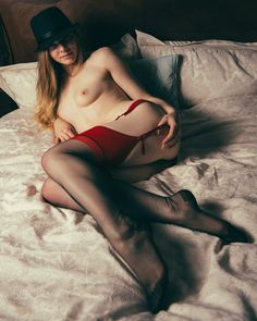 __All that Jazz__ - Alice lies on the top of the sheets on a bed wearing red topped stockings and red suspenders with a black trilby hat on her head.