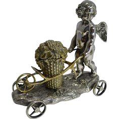 Antique English Silver Plated Cherub Inkwell by Elkington and Co. - Puckerings on Ruby Lane  About as adorable as they get, this fabulous Victorian inkwell featuring a Cherub or Putti figure with a cart holding a basket of flowers, is made by the creme de la creme of English silversmiths, Elkington and Co. The inkwell stands on four revolving wheels, enabling one to roll across the desk top, really for novelty value, so very popular during the Victorian era. Made from English silver plate…