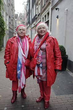 Louise And Martine Fokkens, Amsterdam's Oldest Prostitutes, Retiring At 70 Years Old.  Martine (L) and Louise (R) Fokkens, 70, walk around the red-light district of Amsterdam on November 15, 2012, the Netherlands. Twins Martine and Louise Fokkens, nicknamed the 'Queens of the wallen', are Amsterdam's oldest prostitutes, having worked for fifty years in the city's red-light district. The two have authored two books about their experiences.