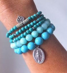 top bracelet. turquoise beads with spacers in center and then charm.