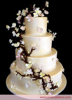 Wedding cake with cascading white and blush pink dogwood flowers. The champagne color was created to contrast the white flowers. They also included petals and blossoms resting upon the individual tiers of the cakes. The cake was delivered to Mountain Ridge Country Club in West Caldwell, NJ. by Dogwood Wedding Cake random-love