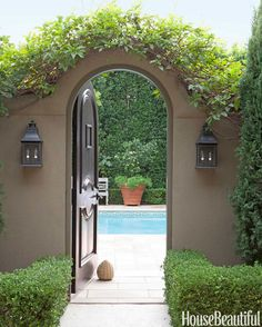 A vine is pruned to enhance the arched doorway in a wall separating the pool and terrace.