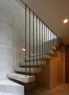 Open riser staircase with thick concrete treads suspended on steel rods.  Residential house, designed by TSC Architects, Mukuoyama, Japan.