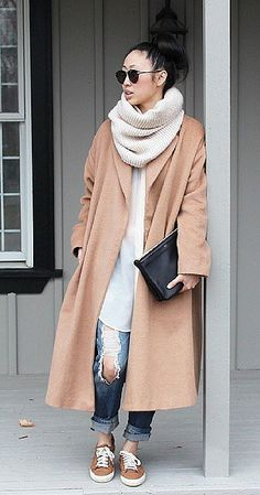 A camel coat paired with boyfriend jeans and a scarf.